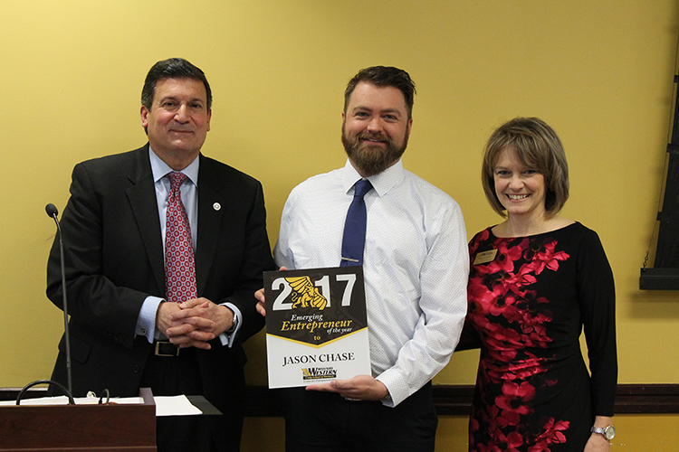 Jason Chase is presented with Emerging Entrepreneur of the Year Award by Annette Weeks and President Dr. Vartabedian